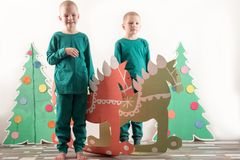 Two funny boys in a Santa Claus hat are playing with horses drawn on cardboard. The guys have fun at home. Christmas holiday conce. Pt. Copy space Royalty Free Stock Image