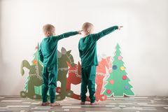 Two funny boys in a Santa Claus hat are playing with horses drawn on cardboard. The guys have fun at home. Christmas holiday conce. Pt. Copy space Royalty Free Stock Photo