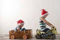 Two funny boys in a Santa Claus hat are playing with horses drawn on cardboard. The guys have fun at home. Christmas holiday conce Stock Photo