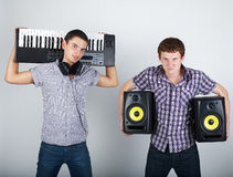 Two funny boys with speakers and piano royalty free stock photo