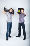 Two funny boys with speakers and piano stock images