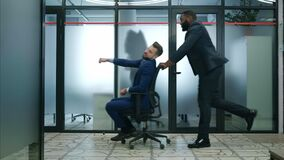 Two funny businessmen riding office chair while having fun in lobby of modern business center. Business people celebrate