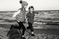 Two funny Caucasian children kids friends playing running on ocean sea beach royalty free stock image