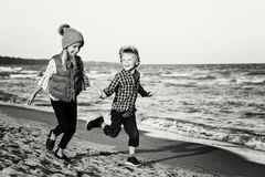 Two funny Caucasian children kids friends playing running on ocean sea beach on sunset stock photos