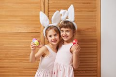 Two funny charming little sisters in the dresses with white rabbit`s ears on their heads holds dyed eggs in their hands stock photography