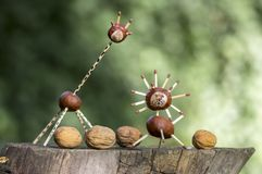 Two funny chestnut animals on tree stump, green background, traditional autumn handcraft, lion and giraffe. Two animals with four walnuts stock photography