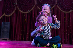 Two funny children acting as monsters on stage. Two funny playful children, boy and girl, smiling while acting as monsters with claws, on a purple stage, in a stock image
