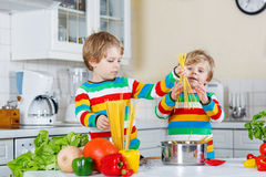 Two funny children cooking italian meal with spahetti Stock Photo