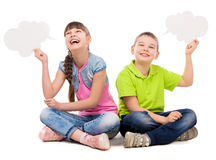 Two funny children sitting on the floor with paper clouds in hands. Laughing isolated on white background Stock Images