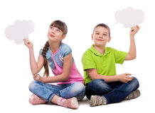 Two funny children sitting on the floor with paper clouds in hands. Laughing  on white background Stock Photo