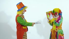 Two funny circus clowns playing with a red glossy box, throwing it to the air. And to each other stock video footage