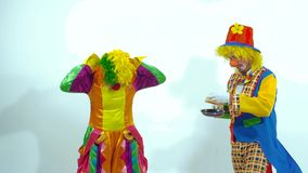 Two funny clowns trying to catch pancakes. Slow motion stock video footage