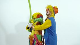Two funny clowns trying to inflate a balloon and tie it stock footage