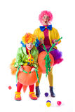 Two funny colorful clown fooling around on a white background Stock Photos