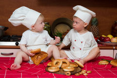 Two funny cooks. Two little babies in the cook costumes at the kitchen sitting on the table Royalty Free Stock Images