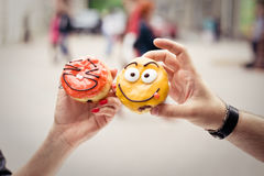 Two funny donuts in man's and woman's hands. Two funny donuts with emotions in man's and woman's hands Stock Images