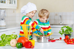 Two funny friends cooking italian meal with spahetti Royalty Free Stock Images