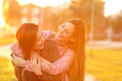 Two funny friends meeting and cuddling in a park royalty free stock photography
