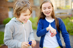 Two funny friends playing with fidget spinners on the playground. Popular stress-relieving toy for school kids and adults. Royalty Free Stock Images