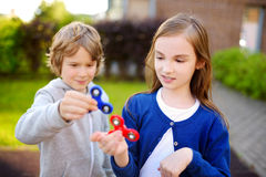 Two funny friends playing with fidget spinners on the playground. Popular stress-relieving toy for school kids and adults. Royalty Free Stock Photos