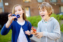 Two funny friends playing with fidget spinners on the playground. Popular stress-relieving toy for school kids and adults. Stock Photos