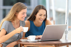 Two friends watching media content in a laptop in a bar Stock Photography