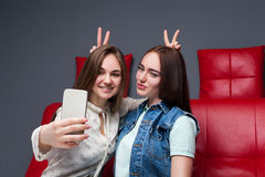 Two funny girlfriends makes selfie on camera Stock Images