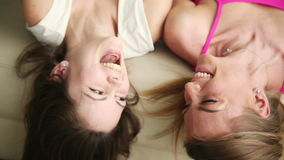 Two funny girlfriends talking and laughing. Top view of two joyful beautiful teen girlfriends hanging out at home, talking and laughing loud. Best friends having stock footage