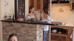 Two funny girls cook in the kitchen of the house. Two friends girls prepare breakfast in the kitchen and feed each other with food from their hands. In the stock video