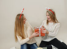 Two funny girls fighting over a gift boxes Stock Photos