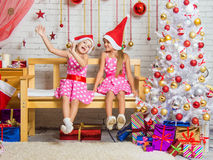 Two funny girls fool around sitting on a bench in a Christmas setting Stock Photography