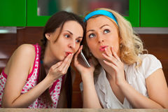 Two funny girls get a phone call in the kitchen Stock Photos