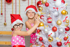 Two funny girls hanging balls on the Christmas tree Stock Photos