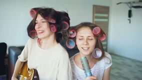 Two funny girls singing with comb and playing electric guitar dance, sing and have joy at home. Two funny girls singing with comb and playing electric guitar in stock video