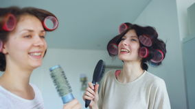 Two funny girls singing with combs dance and have joy in living room at home. Two funny girls singing with combs dance and have joy in living room stock video