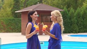 Two women with cocktails relaxing by the pool. Two funny girls in swimsuits and translucent dresses are having fun and relaxing by the pool at a beach party stock video footage