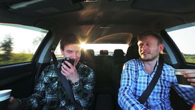 Two funny guys driving fast in the car, drinking coffee, smiling. In full HD stock video