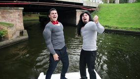 Two funny guys in fake muscle padded costumes dance in boat moving nearby bridge