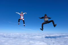 Two funny guys are falling above white clouds. stock photos