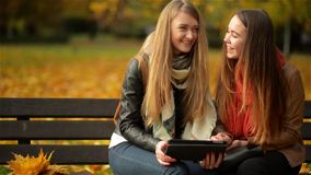Two Funny Happy Young Girls Friends Sitting on the Bench and Using Tablet. Women Laughing and Playing on Pad Computer in stock footage