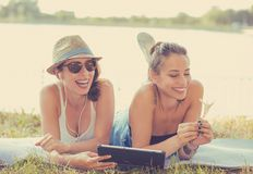 Two funny happy young women friends enjoying summer day outdoors. Two funny happy young women. Friends laughing browsing watching social media videos listen to stock photography