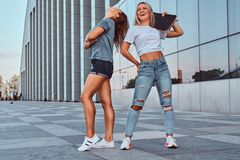 Two funny hipster girls standing with a skateboard on background of the skyscraper. royalty free stock photography