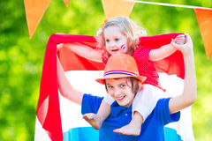 Two funny kids Dutch celebration national holiday. Two Dutch children, teenager boy and funny little girl, celebrating national holiday of Netherlands playing in Royalty Free Stock Images