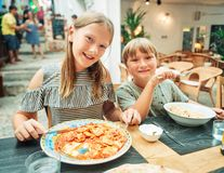 Outdoor summer portrait of two funny kids. Two funny kids having lunch in the restaurant, eating ravioli and pasta royalty free stock images