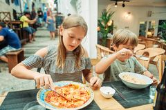 Two funny kids having lunch in the restaurant. Eating ravioli and pasta stock photography
