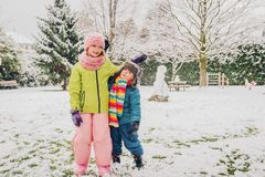 Two funny kids playing together outside. Two adorable kids playing together in snow park, wearing warm winter clothes Stock Photography
