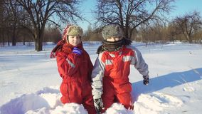 Two funny kids playing together at snow stock video
