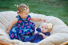 Two funny kids sitting in the soft light chair together in spring park Royalty Free Stock Images