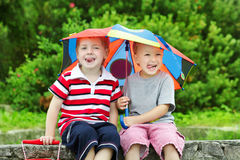 Two funny kids and umbrella. Summer rain Stock Image