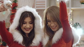 Two funny ladies dancing, smiling with Christmas toys. In full HD stock video